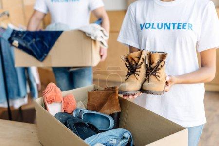 Photo pour Vue recadrée de bénévoles multiculturels déballant des boîtes en carton avec des vêtements et des chaussures - image libre de droit