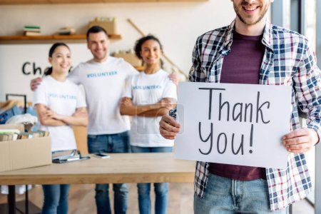 Photo for Partial view of man holding card with thank you text while standing near multicultural volunteers in charity center - Royalty Free Image