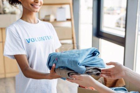 Photo pour Vue recadrée de volontaire américain africain donnant des vêtements à la femme dans le centre de charité - image libre de droit