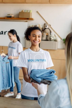 selective focus of cheerful african american volunteer girl giving clothes to woman