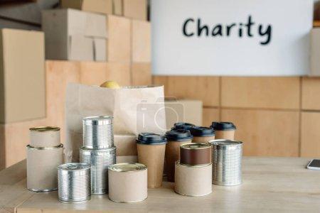 Photo pour Nourriture en conserve, tasses jetables et sac en papier sur la table en bois dans le centre de charité - image libre de droit