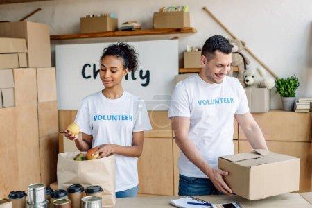 Photo pour Jolie fille afro-américaine mettant des pommes dans le sac en papier tandis que beau volontaire retenant la boîte de carton - image libre de droit