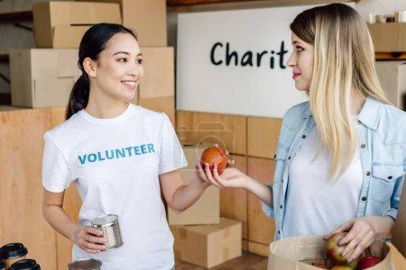 Photo pour Bénévole asiatique gai donnant de la nourriture en conserve et des pommes à la femme dans le centre de charité - image libre de droit