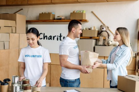 Photo for Young multicultural volunteers giving food to pretty woman in charity center - Royalty Free Image