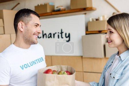 Photo pour Beau, bénévole souriant donnant sac en papier avec des pommes à la femme attirante - image libre de droit