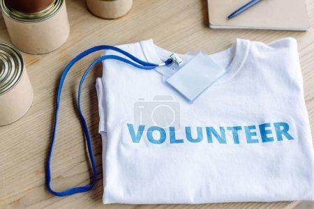 Photo pour T-shirt blanc avec inscription bleue de volontaire, insigne et étuis sur table en bois - image libre de droit