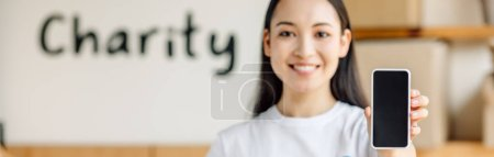 Photo for Panoramic shot of young, smiling asian volunteer holding smartphone with blank screen - Royalty Free Image