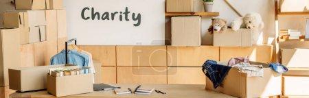 Photo pour Plan panoramique de boîtes en carton avec livres et vêtements, armoires en bois et pancarte avec inscription caritative - image libre de droit