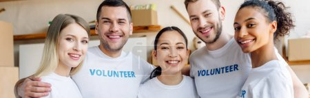 Photo for Panoramic shot of young, cheerful volunteers hugging and looking at camera - Royalty Free Image