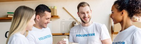 Photo for Panoramic shot of young multicultural volunteers smiling and talking in charity center - Royalty Free Image