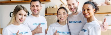 Photo for Panoramic shot of young, cheerful volunteers showing thumbs up and looking at camera - Royalty Free Image