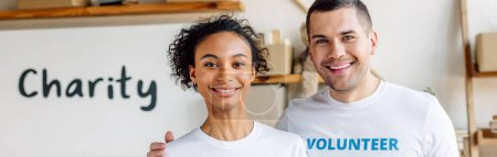 Photo pour Photo panoramique de jeunes volontaires multiculturels souriant et regardant l'appareil-photo - image libre de droit