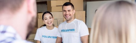 Photo for Panoramic shot of smiling multicultural volunteers meeting people in charity center - Royalty Free Image