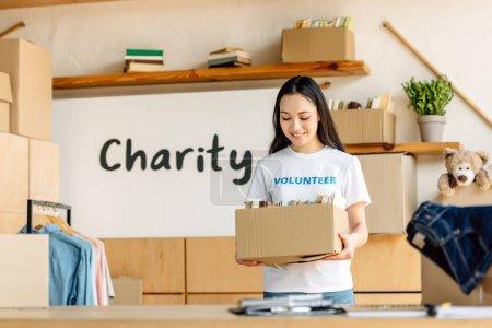 Photo pour Joli volontaire asiatique tenant boîte en carton tout en se tenant près de la plaque avec l'inscription de charité - image libre de droit