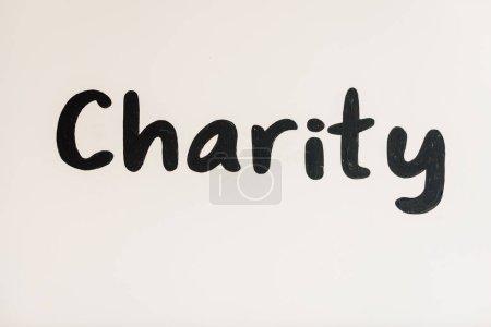 Photo pour Inscription de charité manuscrite noire sur blanc avec espace de copie - image libre de droit