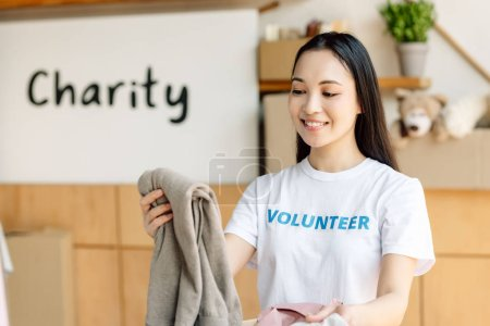 Photo pour Young, smiling asian volunteer holding clothes while standing near placard with charity inscription - image libre de droit