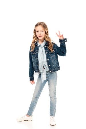 Photo for Full length view of kid in jeans showing peace sign on white - Royalty Free Image