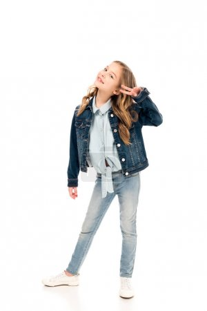 Photo pour Full length view of kid in denim clothes showing peace sign on white - image libre de droit