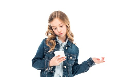 concentrated kid in denim jacket using smartphone isolated on white