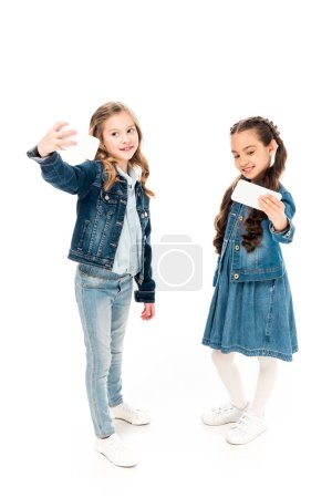 Photo for Full length view of kids in denim clothes taking selfie on white - Royalty Free Image