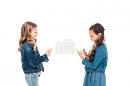 Photo pour Deux enfants en vêtements denim en utilisant des smartphones isolés sur blanc - image libre de droit