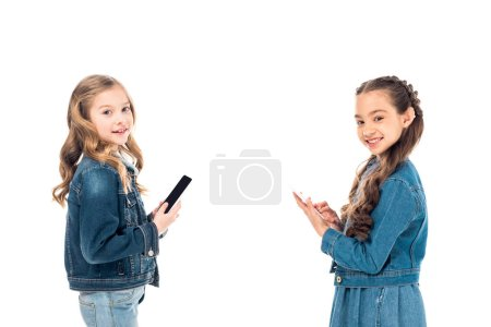 Photo for Two kids in denim clothes using smartphones isolated on white - Royalty Free Image