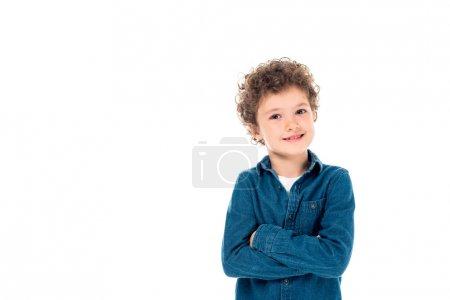 Photo pour Enfant bouclé souriant en chemise en denim debout avec les bras croisés isolés sur blanc - image libre de droit