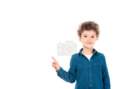 Photo pour Front view of smiling kid in denim shirt pointing with finger isolated on white - image libre de droit