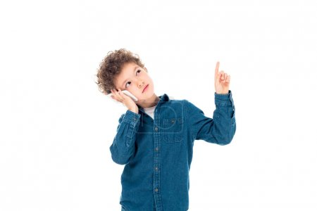 Photo for Pensive curly kid in denim shirt talking on smartphone and showing idea sign isolated on white - Royalty Free Image
