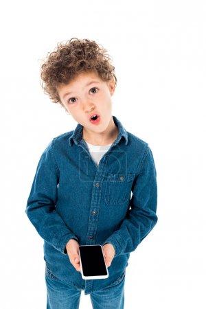 Photo pour Enfant étonné dans le smartphone de fixation de chemise de denim avec l'écran blanc d'isolement sur le blanc - image libre de droit