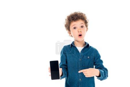 Photo pour Vue de face d'un enfant choqué en chemise en denim pointant avec le doigt vers un smartphone avec écran vierge isolé sur blanc - image libre de droit