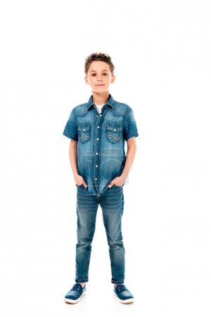 full length view of kid in denim clothes standing with hands in pockets isolated on white