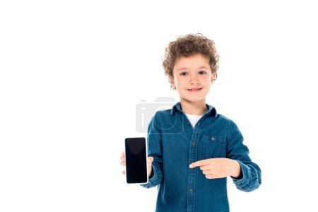 Photo for Front view of curly child in denim shirt pointing with finger at smartphone with blank screen isolated on white - Royalty Free Image