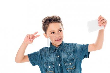 Photo pour Enfant dans la chemise de denim prenant le selfie et affichant le signe de paix d'isolement sur le blanc - image libre de droit