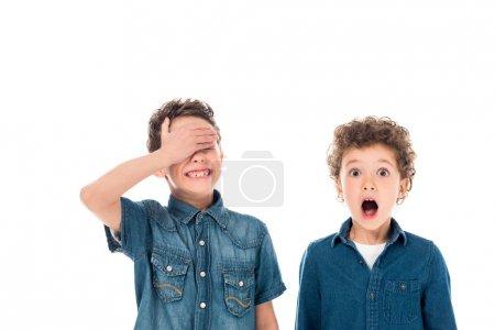 Foto de Shocked curly boy posing with friend isolated on white - Imagen libre de derechos
