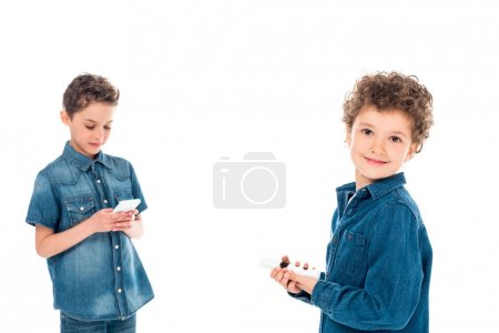 Photo for Two kids in denim shirts using smartphones isolated on white - Royalty Free Image