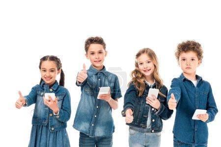 Foto de Cuatro niños vestidos de mezclilla usando teléfonos inteligentes y mostrando los pulgares hacia arriba aislados en blanco - Imagen libre de derechos