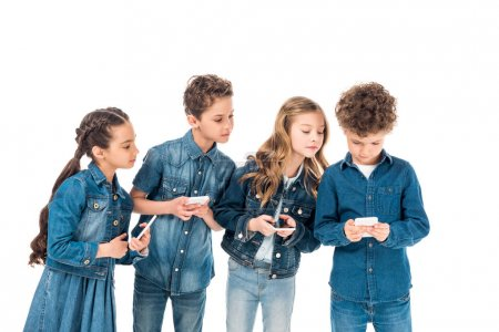 Photo for Four kids in denim clothes using smartphones isolated on white - Royalty Free Image