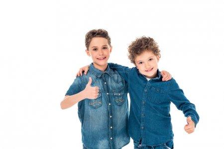 Photo pour Deux enfants en chemises denim embrassant et montrant pouces isolés sur blanc - image libre de droit