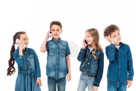 Photo pour Quatre enfants dans des vêtements en denim parlant sur des smartphones isolés sur le blanc - image libre de droit
