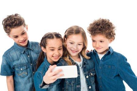 Foto de Cuatro niños sonrientes en ropa de mezclilla tomando selfie aislado en blanco - Imagen libre de derechos