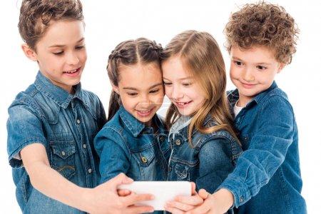 Photo pour Four smiling kids in denim clothes taking selfie isolated on white - image libre de droit
