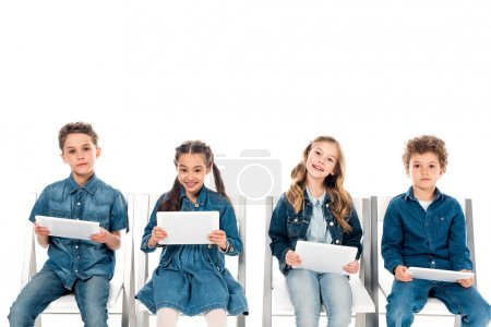 Photo pour Four smiling kids in denim clothes sitting on chairs and using digital tablets isolated on white - image libre de droit