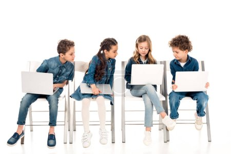 Photo for Four kids in denim clothes sitting on chairs and using laptops on white - Royalty Free Image