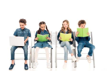 Photo pour Sourire garçon en utilisant un ordinateur portable tandis que ses amis lisant des livres sur blanc - image libre de droit