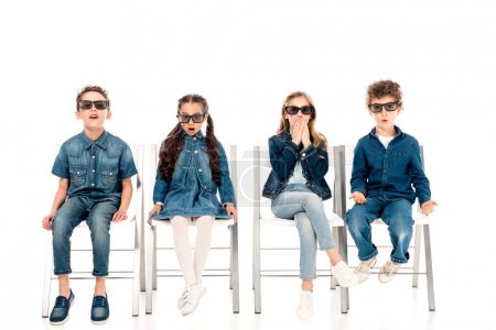 Foto de Cuatro niños sorprendidos en gafas 3d sentados en sillas en blanco - Imagen libre de derechos