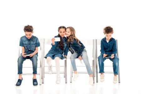 Foto de Niños con ropa de mezclilla sentados en sillas y tomar selfie en blanco - Imagen libre de derechos