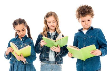 Photo pour Trois enfants concentrés dans des vêtements en denim lisant des livres isolés sur le blanc - image libre de droit