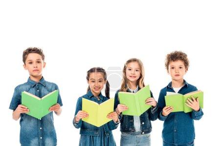 Foto de Cuatro niños con ropa de mezclilla sosteniendo libros aislados en blanco - Imagen libre de derechos