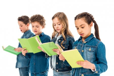 Foto de Four amazed children in denim clothes reading books isolated on white - Imagen libre de derechos